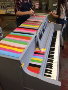 Top view of a piano being painted colorfully.